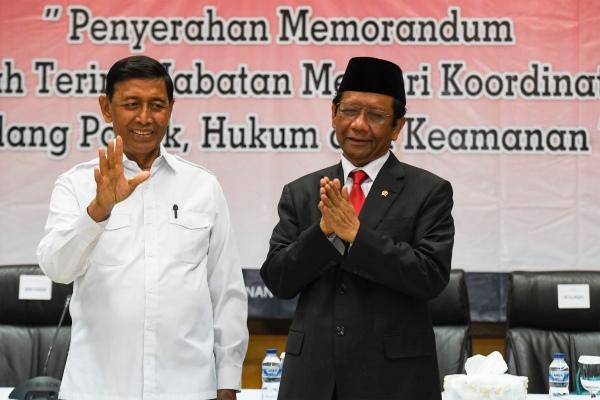 Menko Polhukam Mahfud MD (kiri) bersama mantan Menko Polhukam Wiranto (kanan) mengikuti serah terima jabatan di kantor Kemenko Polhukam, Jakarta, Rabu (23/10/2019) - ANTARA FOTO/Hafidz Mubarak A