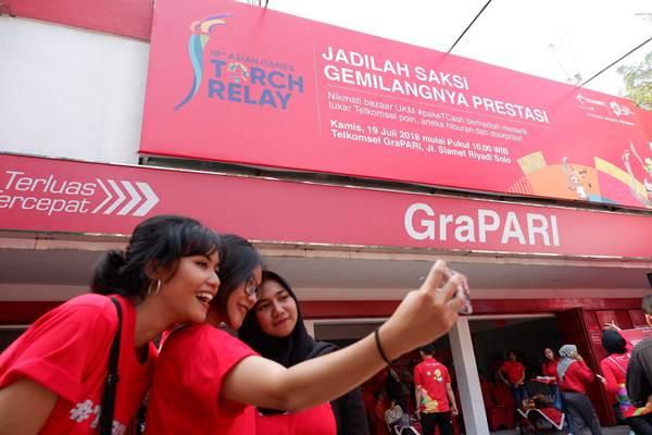 Warga kota Solo antusias menyambut rombongan pawai obor Asian Games 2018 yang berkesempatan disambut di GraPARI Solo, (19/7). Sebagai Official Mobile Partner Asian Games 2018, Telkomsel turut berpartisipasi dalam menyukseskan kegiatan pawai obor yang diselenggarakan di sejumlah kota di Indonesia. - Telkomsel