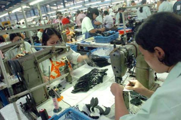 Pekerja pabrik menyelesaikan proses produksi sepatu. - Bisnis.com