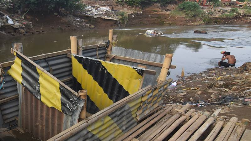 Seorang warga mandi di dekat bilik kakus atau jamban di kawasan Kampung Melayu, Jakarta, Rabu (16/10/2019). Pemerintah Provinsi DKI Jakarta mengajukan anggaran Rp 10 miliar untuk memberantas kebiasaan buang air besar atau BAB sembarangan melalui program rehabilitasi septic tank dalam Kebijakan Umum Anggaran-Prioritas Plafon Anggaran Sementara (KUA-PPAS) untuk rancangan APBD DKI 2020.  - Antara