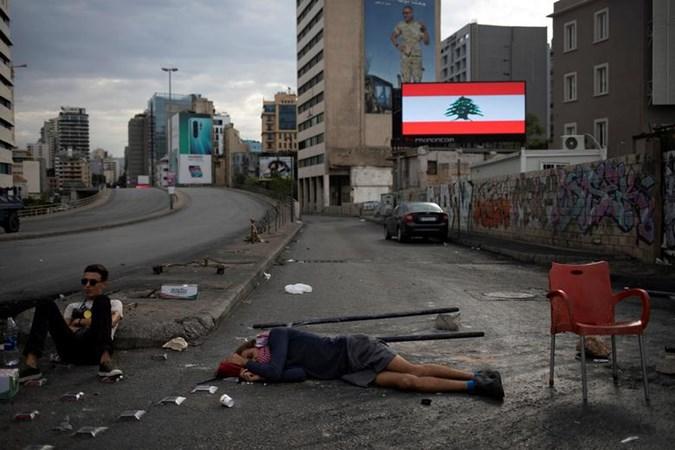 Seorang demonstran bersandar di tanah ketika ia dan demonstran lainnya memblokir jalan raya selama protes anti-pemerintah yang sedang berlangsung di pusat kota Beirut, Lebanon, 23 Oktober 2019. - REUTERS/Alkis Konstantinidis