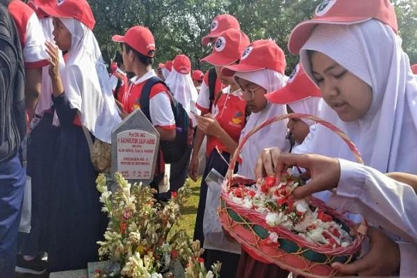 Para pelajar menabur bunga di makam Presiden ke-3 RI BJ Habibie di TMP Kalibata, Jakarta, Selasa (5/11/2019) pada acara ziarah wisata dalam rangka peringatan Hari Pahlawan 2019. - Antara