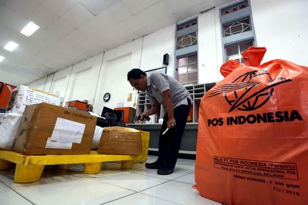 Pekerja mendata paket barang sebelum dialihkan ke pusat pemrosesan pos untuk dikirim ke tujuan, di Kantor Pos Besar Bandung, Jawa Barat, Rabu (6/6/2018). - JIBI/Rachman