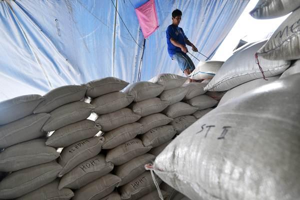 Pekerja memindahkan karung berisi beras di Pasar Induk Beras Cipinang, Jakarta Timur, Jumat (19/1). - ANTARA/Sigid Kurniawan
