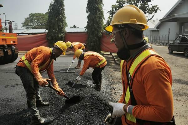 Pekerja menyelesaikan proses pengaspalan di sela-sela peresmian penerapan aspal plastik di area pabrik PT Chandra Asri Petrochemical Tbk (CAP) di Cilegon, Banten, Selasa (3/7/2018). - Bisnis/Felix Jody Kinarwan
