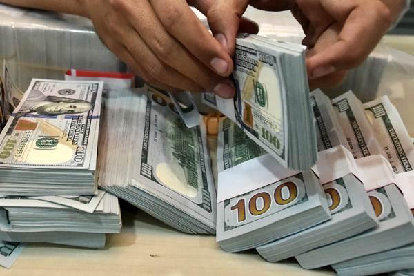 Petugas menghitung pecahan dolar AS di salah satu gerai penukaran mata uang asing, di Jakarta. - JIBI/Abdullah Azzam