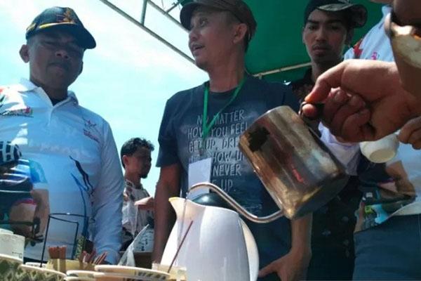 Aksi kopi gratis mewarnai balap sepeda Tour de Singkarak di Sumatra Barat pada Kamis (7/11/2019). - Antara
