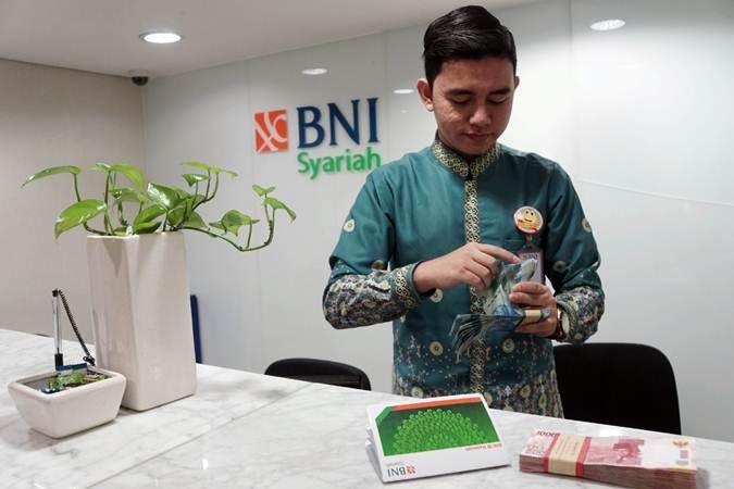 Karyawan menghitung uang di salah satu kantor cabang Bank BNI Syariah (BNIS) di Jakarta, Senin (1/7/2019). - Bisnis/Himawan L Nugraha
