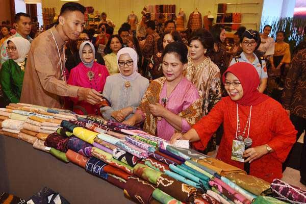 Ibu Negara Iriana Joko Widodo (kedua kanan) bersama Istri Wapres Mufidah Jusuf Kalla (ketiga kiri) meninjau stan Pameran Karya Kreatif Indonesia usai pembukaannya di JCC, Jakarta, Jumat (18/8). Pameran tersebut menampilkan kain dan kerajinan UMKM binaan Bank Indonesia. ANTARA FOTO - Akbar Nugroho Gumay