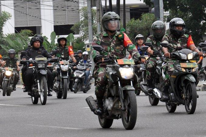 Sejumlah personel Polri bersama prajurit TNI melakukan patroli pengamanan bersama melintasi Jalan Balaikota Medan, Sumatera Utara, Sabtu (19/10/2019). - ANTARA/Septianda Perdana