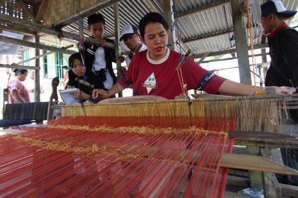 Sejumlah siswa melihat proses pembuatan tenunan kain songket Batubara saat berkunjung di Batubara, Sumatera Utara, Rabu (3/8/2016). Sebanyak 19 pelajar berprestasi asal Sulawesi Barat tersebut melakukan perjalanan ke Sumut sebagai bagian dari program Siswa Mengenal Nusantara yang bertujuan seluruh siswa dapat mengenal budaya, adat istiadat dan memberikan wawasan yang lebih luas dalam mengenal nusantara. - Antara/Septianda Perdana