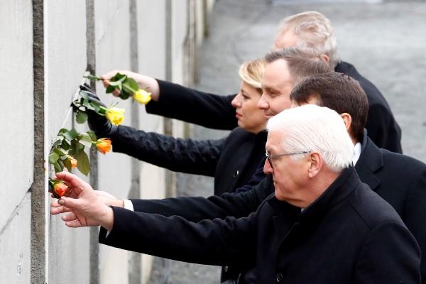 Presiden Jerman Frank-Walter Steinmeier, Presiden Hungaria Janos Ader, Presiden Polandia Andrzej Duda, Presiden Slovakia Zuzana Caputova, dan Presiden Republik Ceko Milos Zeman menaruh bunga mawar di celah tembok yang dijadikan simbol Tembok Berlin dalam upacara peringatan 30 tahun jatuhnya Tembok Berlin di Berlin, Jerman, Sabtu (9/11/2019). - Reuters/Fabrizio Bensch