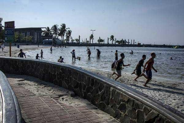 Wisatawan menikmati suasana di kawasan pantai Ancol, kompleks Taman Impian Jaya Ancol, Jakarta, Rabu (4/10). - ANTARA/Aprillio Akbar