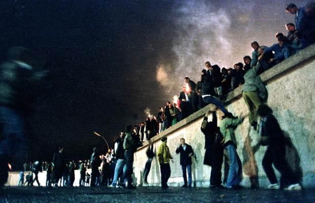 Warga Jerman Timut memanjat tembok Berlin di Gerbang Brandeburg setelah pengumuman pembukaan perbatasan Jerman Timur, 10 November 1989. - REUTERS
