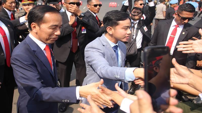 Presiden Joko Widodo (kiri) didampingi putranya Gibran Rakabuming (kanan) menyalami warga sebelum mengikuti upacara pelantikan Presiden dan Wakil Presiden periode 2019-2024 di Jakarta, Minggu (20/10/2019). - Antara