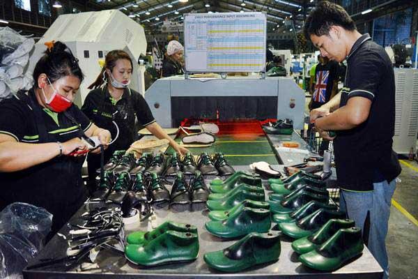 Pekerja menyelesaikan pembuatan sandal dan sepatu di PT Aggiomultimex, Sidoarjo, Jawa Timur, Senin (25/9/2017). - ANTARA/Umarul Faruq