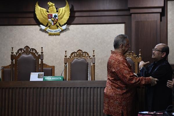 Mantan Dirut PLN Sofyan Basir (kiri) berjabat tangan dengan kuasa hukumnya usai pembacaan putusan di Pengadilan Tipikor, Jakarta, Senin (4/11/2019). Majelis hakim memvonis bebas Sofyan Basir - ANTARA FOTO/Puspa Perwitasari