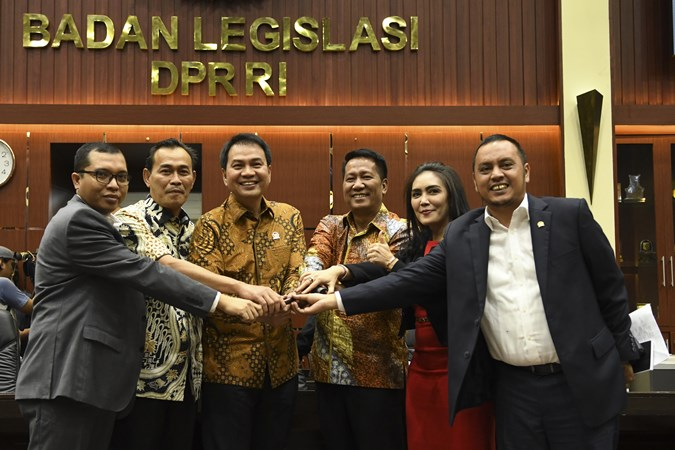 Wakil Ketua DPR Bidang Korpolkam Azis Syamsuddin (ketiga kiri) berjabat tangan bersama Ketua Badan Legislasi (Baleg) periode 2019-2024 Supratman Andi Agtas (ketiga kanan) dan Wakil Ketua Ibnu Multazam (kedua kiri), Willy Aditya (kanan), Achmad Baidowi (kiri) dan Rieke Diah Pitaloka (kedua kanan) usai penetapan Ketua Baleg di ruang Banggar, Kompleks Parlemen, Jakarta, Rabu (30/10/2019). - ANTARA/Muhammad Adimaja