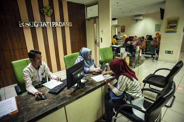 Petugas melayani calon pasien menyelesaikan proses administrasi di RSUD Jati Padang, Jakarta, Senin (7/1/2019). - ANTARA/Aprillio Akbar