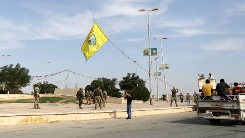 Pejuang pemberontak Suriah yang didukung Turki menurunkan bendera Dewan Militer Tel Abyad di kota perbatasan Tel Abyad, Suriah, 14 Oktober 2019. - Reuters