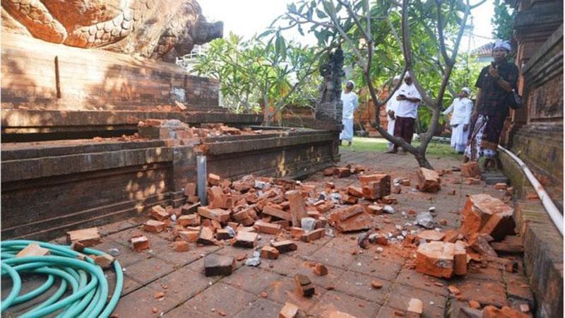 Pemuka agama Hindu memantau kerusakan pada bagian candi yang runtuh akibat gempa di Pura Lokanatha, Denpasar, Bali, Selasa (16/7/2019).. - Antara/Nyoman Budhiana