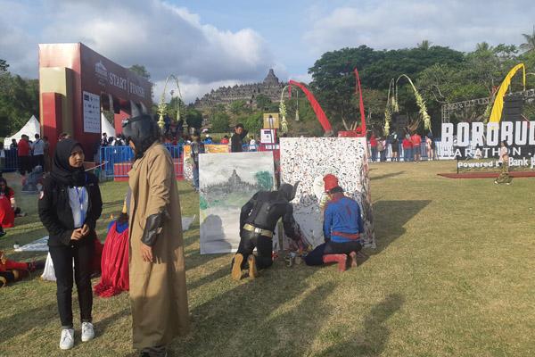Para seniman lukis yang bergaya layaknya super hero turut menyemarakkan acara Borobudur Marathon 2019 hari Minggu 17 November 2019. Selain kostum yang unik, mereka menunjukkan kebolehannua dalam membuat lukisan Candi Borobudur. - Bisnis/Hafiyyan