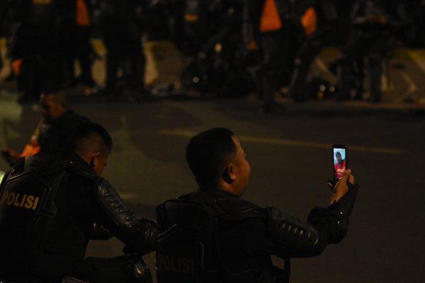 Seorang anggota Brimob Polda Kalimantan Utara Jufri melakukan telepon video dengan anaknya saat beristirahat sejenak dari pengamanan aksi unjuk rasa di depan gedung Parlemen, Jakarta, Senin (30/9/2019). - ANTARA FOTO/Indrianto Eko Suwarso