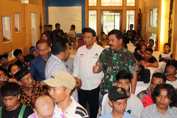 Menko Polhukam Wiranto (tengah) didampingi Panglima TNI Marsekal Hadi Tjahjanto (kanan) berbincang dengan pengungsi Wamena dan Ilaga di Timika, Mimika, Papua, Rabu (9/10/2019). Dalam kesempatan itu para pengungsi meminta agar mereka difasilitasi kembali ke kampung halaman masing-masing. - Antara/Sevianto Pakiding