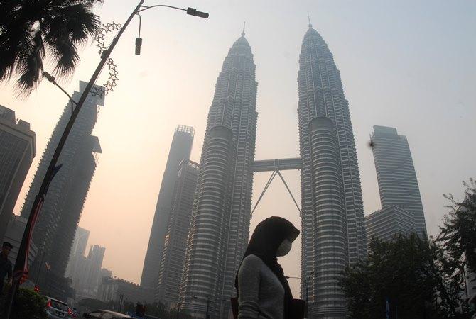 Warga beraktivitas dengan mengenakan masker di dekat menara kembar Petronas, Kuala Lumpur, Malaysia, Selasa (10/9/2019). - ANTARA / Rafiuddin Abdul Rahman