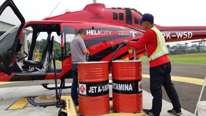 Dua orang pekerja sedang melakukan pengisian bahan bakar helikopter jenis Bell 505 milik Helicity di Kompleks Pusdirga, Senin (3/6/2019).  - Istimewa