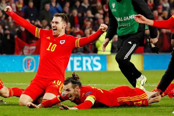 Dua pemain andalan Wales, Aaron Ramsey (kiri) dan Gareth Bale, merayakan kesuksesan timnya lolos ke putaran final Euro 2020. - Reuters/Andrew Boyers