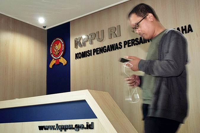 Karyawan melintas di dekat logo Komisi Pengawas Persaingan Usaha (KPPU), di Jakarta, Kamis (18/7/2019). - Bisnis/Himawan L Nugraha