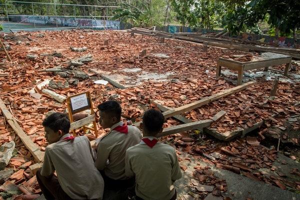 Pelajar melihat reruntuhan bangunan aula sekolah yang roboh di SMK Negeri I Miri, Sragen, Jawa Tengah, Kamis (21/11/2019). Bangunan aula sekolah tersebut roboh akibat hujan dan angin kencang yang menyebabkan 22 siswa mengalami luka-luka karena tertimpa reruntuhan bangunan. - Antara/Mohammad Ayudha