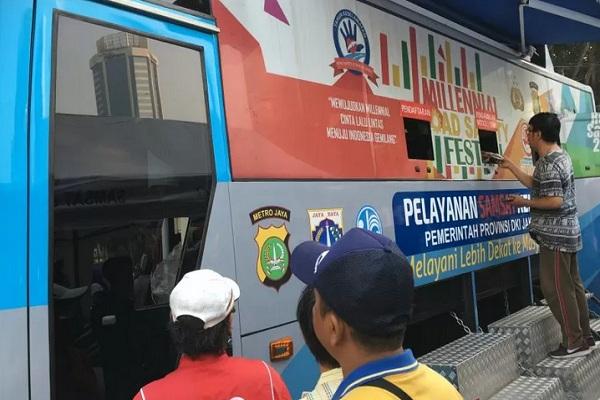 Warga melalukan transaksi perpanjangan pajak kendaraan bermotor di mobil SAMSAT keliling di car free day Bundarah HI, Jakarta, Minggu (28/7). - Antara