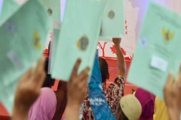 Warga masyarakat mengangkat sertifikat tanah dalam program sertifikasi tanah yang digelar oleh Kementerian Agraria dan Tata Ruang