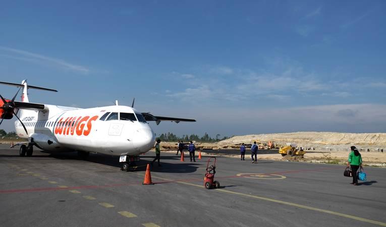 Penumpang bersiap naik ke pesawat dengan latar belakang proyek pembangunan perluasan Bandara Internasional Raja Sisingamangaraja XII (sebelumnya bernama Silangit), di Tapanuli Utara, Sumatra Utara, Selasa (19/3/2019). - ANTARA/Irsan Mulyadi