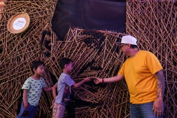 Seniman Nus Salomo (kanan) menjelaskan hasil karyanya kepada anak/anak tentang instalasi bambu berbentuk wajah Ir Soekarno yang dipamerkan pada aksi BNI KEJAR atau Kenali Sejarah Raihlah Mimpimu di Terowongan Dukuh Atas, Jakarta, Minggu (24 November 2019). Aksi BNI KEJAR kali ini digelar dalam rangka memperingati Hari Kesehatan & Hari Pahlawan Nasional selama sepekan mulai 24 November hingga 1 Desember 2019.