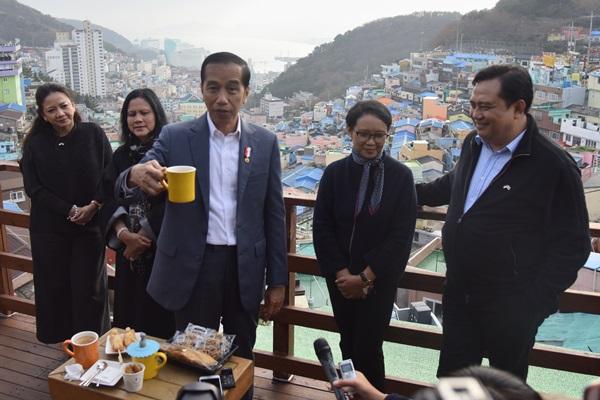 Presiden Jokowi didampingi Ibu Negara, Menlu, dan Dubes RI di Seoul, menikmati kopi di salah satu kafe saat mengunjungi Gamcheon Culture Village, di Busan, Minggu (24/11) sore - setkab.go.id