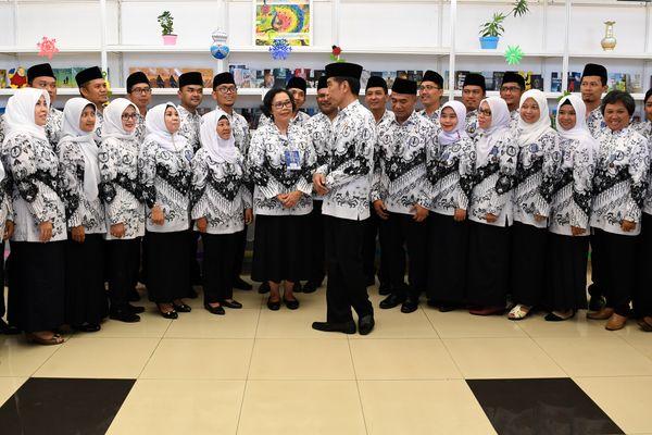 Presiden Joko Widodo (tengah) berjabat tangan dengan guru penerima penghargaan pada peringatan Hari Ulang Tahun ke-73 Persatuan Guru Republik Indonesia, di Stadion Pakansari, Jawa Barat, Sabtu (1/12/2018). - Antara/Puspa Perwitasari