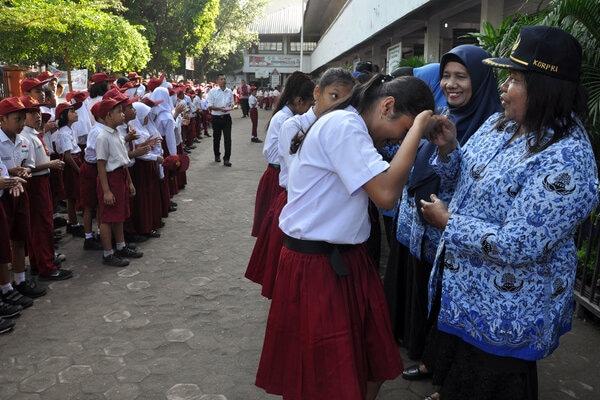 Sejumlah siswa menyalami guru mereka seusai mengikuti upacara di Sekolah Dasar Negeri 060813 Medan, Sumatera Utara, Senin (25/11/2019). Menyalami guru oleh para siswa tersebut dalam rangka memperingati Hari Guru yang serentak dilaksanakan di seluruh Indonesia. - Antara/Septianda Perdana