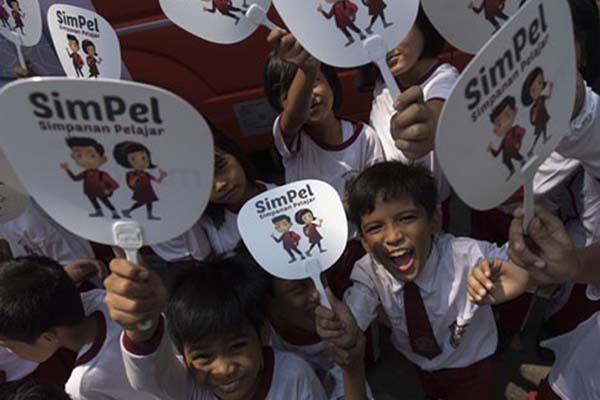 Para siswa sekolah dasar menunjukkan logo tabungan SimPel - Antara/Rosa Panggabean
