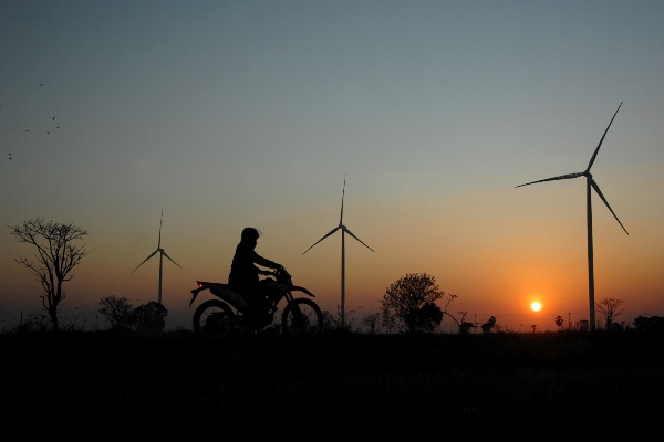 Warga melintas menggunakan kendaraan roda dua di sekitar Pembangkit Listrik Tenaga Bayu (PLTB) Jeneponto dengan latar suasana matahari tenggelam (sunset) di Kecamatan Binamu, Kabupaten Jeneponto, Sulawesi Selatan, Rabu (23/10/2019). - ANTARA FOTO/Abriawan Abhe