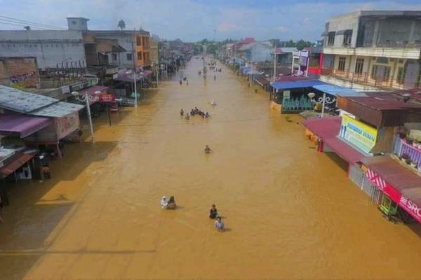Warga melintasi banjir yang menggenangi Kota Pasir Pangaraian, Rokan Hulu, Riau, Selasa (26/11/2019). Banjir yang semakin meluas di Rohan Hulu itu memutus akses jalan utama di wilayah tersebut. - Antara/Humas Rokan Hulu