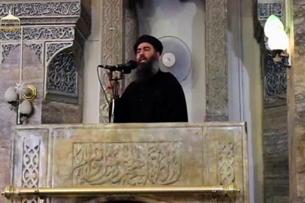 Seorang pria yang diyakini sebagai pemimpin ISIS Abu Bakar Al-Baghdadi berbicara di sebuah masjid di Mosul, Irak, dalam sebuah foto yang diambil dari video yang ditayangkan di internet pada Sabtu (5/7/2014). - Reuters