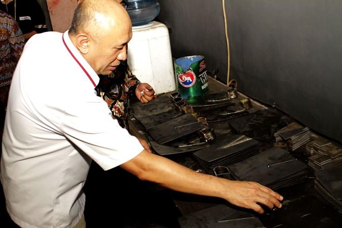 Menteri Koperasi dan Usaha Kecil Menengah (UKM) Teten Masduki memeriksa cangkul buatan UKM Desa Cibatu, Kecamatan Cisaat di Sukabumi, Jawa Barat, Sabtu (23/11/2019). - ANTARA / Budiyanto