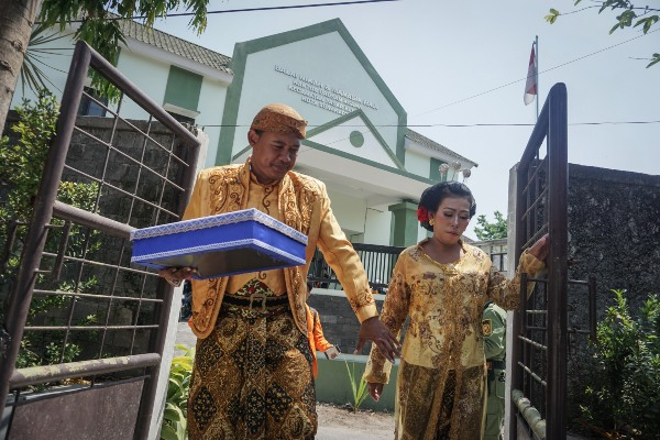 Pasangan peserta nikah massal berjalan keluar dari Kantor Urusan Agama (KUA) usai mengikuti acara Nikah Massal Warga Mojo, Pasar Kliwon, Solo, Jawa Tengah, Selasa (29/10/2019). - ANTARA FOTO/Mohammad Ayudha