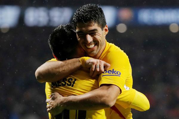 Lionel Messi mendapat pelukan dari Luis Suarez setelah mencetak gol kemenangan Varcelona atas Atletico Madrid. - Reuters/Susana Vera