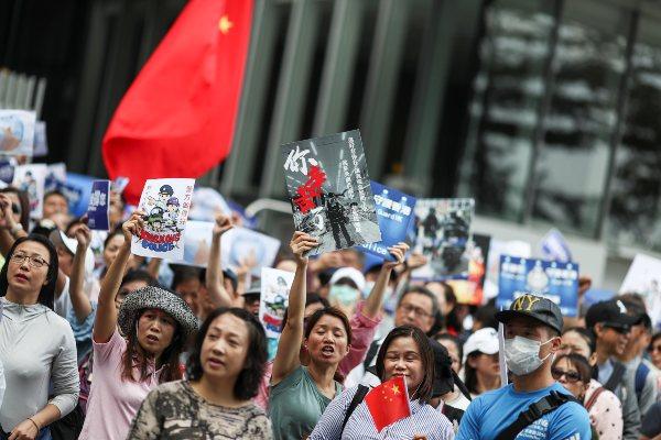 Warga Hong Kong pro China mengibarkan bendera China dan berbagai poster dalam aksi unjuk rasa mendukung Beijing serta polisi Hong Kong di gedung Dewan Legislatif di Hong Kong, China, Sabtu (16/11/2019). - Reuters/Athit Perawongmetha