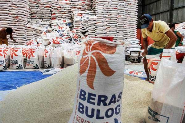 Pekerja mengisi beras kedalam karung di Gudang Bulog Divisi Regional Riau - Kepulauan Riau di Pekanbaru, Riau, Rabu (18/4/2018). - ANTARA/Rony Muharrman