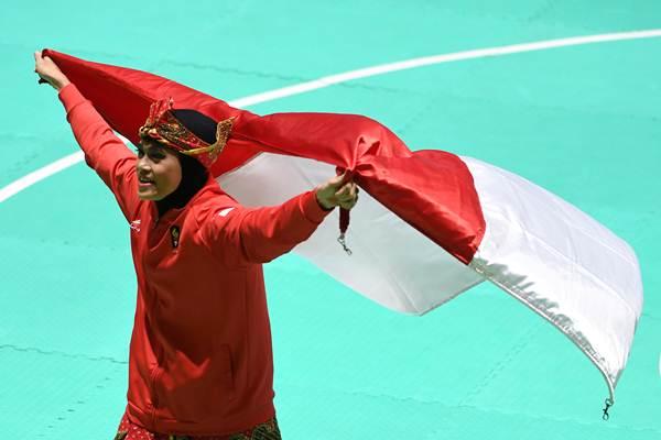 Pesilat Indonesia Puspa Arumsari membentangkan bendera Merah Putih. - ANTARA/Melvinas Priananda